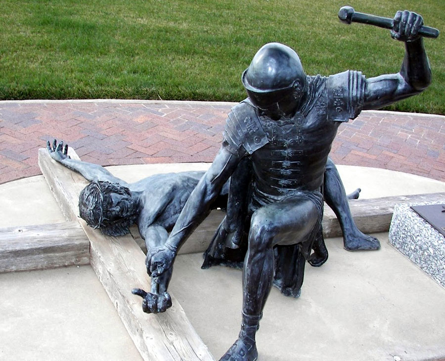 statue of jesus being nailed to cross